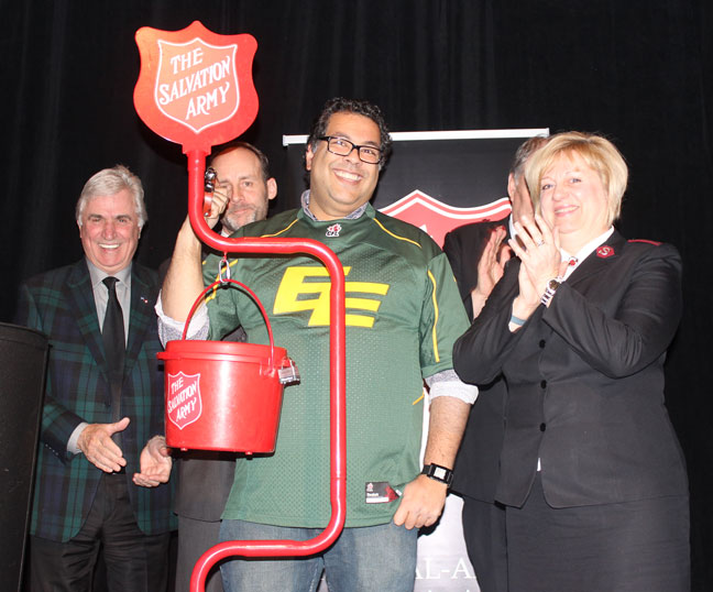 Mayor Naheed Nenshi makes a donation to the Army at the Calgary's Hope in the City event, as Cpt Pamela Goodyear, DSPRD, Alta. & N.T. Div, applauds