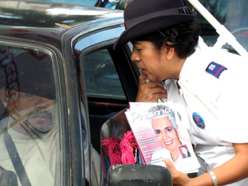 A cadet prays with a driver and distributes anti-trafficking literature