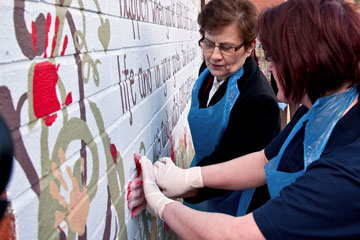 General Linda Bond adds a palm-print to the mural wall next to the Growing Together community gardens
