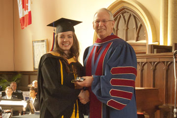 Commissioner Brian Peddle presents the Chancellor's Medal to Booth UC graduate Rebecca Peters