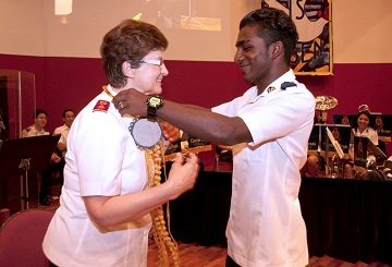 General Linda Bond is presented with a sandalwood garland by Kishan from the Tamil fellowship from Eratchipuu Corps, Singapore