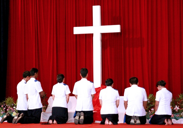 Newly commissioned lieutenants in Myanmar kneel at the foot of the cross to pray