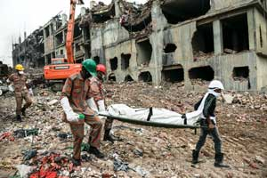 Rescuers carry a body retrieved from the rubble of the Rana Plaza building  (Photo: Ismail Ferdous, The Associated Press)