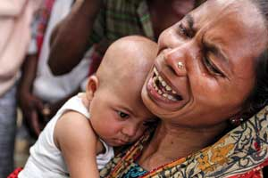 A Bangladeshi woman holds her daughter and weeps (Photo: Palash Khan, The Associated Press)