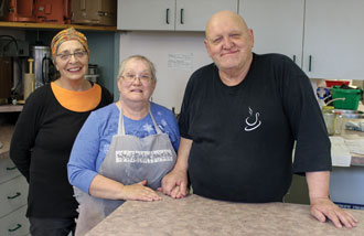 Volunteers Natalie Austin, Nadine Lazenby and Rod Lazenby make delicious meals for the program