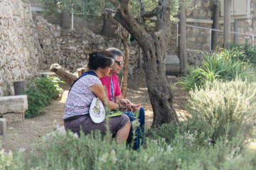 Mjrs Lynn and Brian Armstrong share a moment of prayer in the Garden of Gethsemane