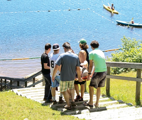 Staff and friends carry Dion Oxford down a steep hill to the lake at Camp Koinonia