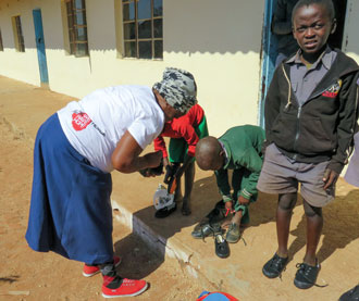 Moyo helps children try on their new shoes