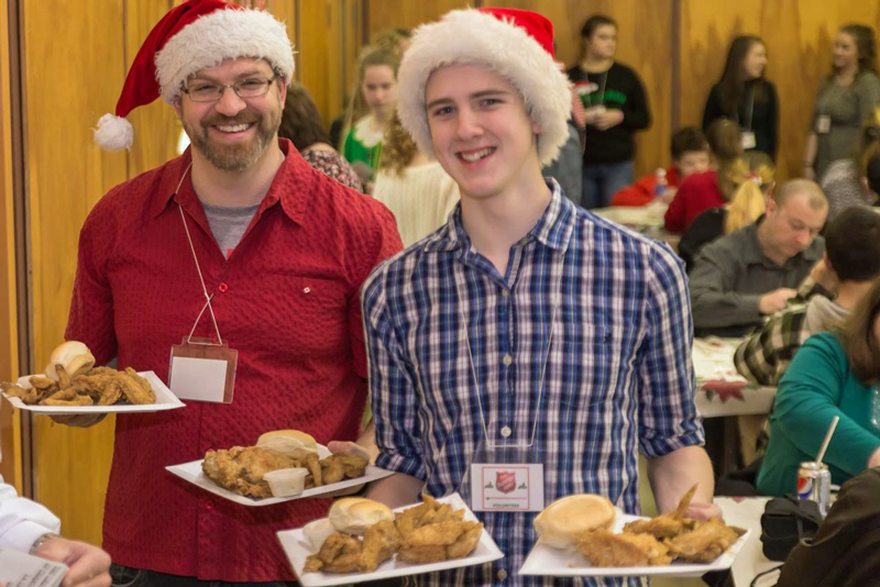 Two volunteers show off the main course at the Christmas supper hosted by St. John's Temple