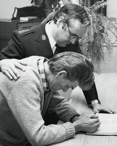 Photo of then-Captain Weldon Carr counselling a man in the chapel of the Richmond Street Rehabilitation Centre in Toronto, circa 1980