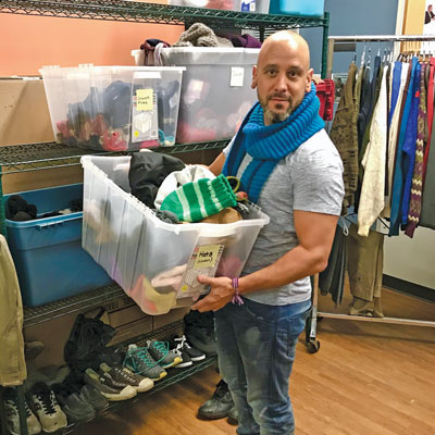 Brian Shurman organizes the clothing room at The Gateway shelter in Toronto