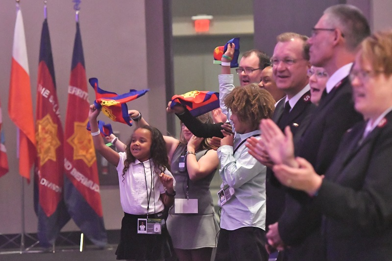 Children wave glory flags at the conclusion of commissioning weekend