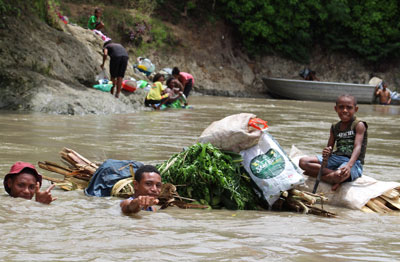 "Papua New Guineans float ""garden foods"" down the river to be sold at the market"