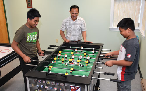 Joseph Paway and his sons Richwill and Lemuel enjoy a game of foosball in the youth room at Woodstock CC
