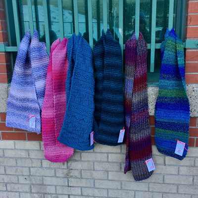 Scarves made by CommuKNITy Cares volunteers  left on fences.