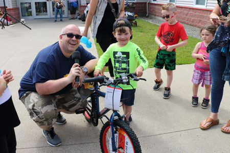 Major Corey Vincent gives a child a bicycle