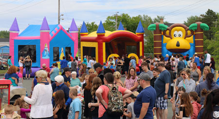 A large crowd of people gathers near bouncy castles at the block party