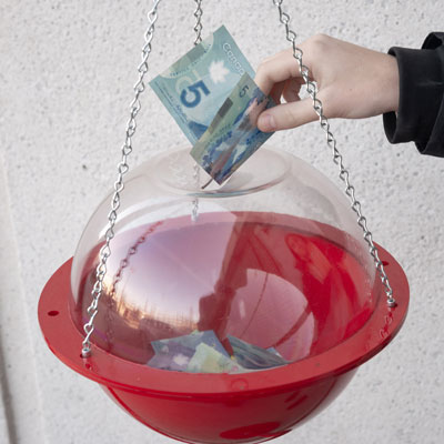 A hand puts a five-dollar bill in a Salvation Army kettle