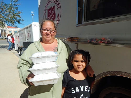 Jolynn and her daughter receive food from a Salvation Army canteen