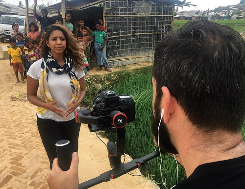 A cameraman films Molly Thomas as she reports from a refugee camp in Bangladesh