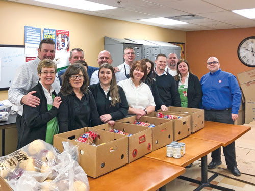 A group of Sobeys employees, with Major Corey Vincent, stand next to a table of Christmas hampers