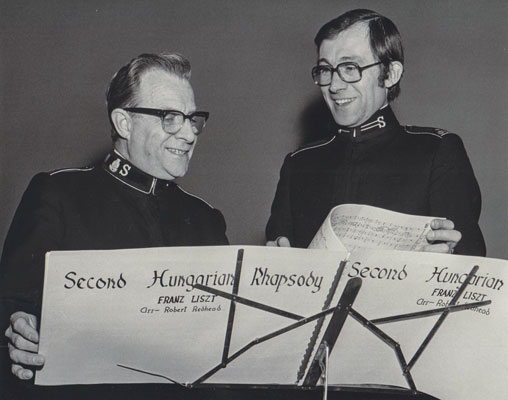 Then Captain Robert Redhead poses with Commissioner Arnold Brown by a pair of music stands
