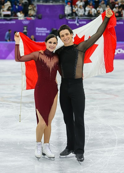 Tessa Virtue and Scott Moir proudly holding the Canadian flag at the 2018 Olympic Games