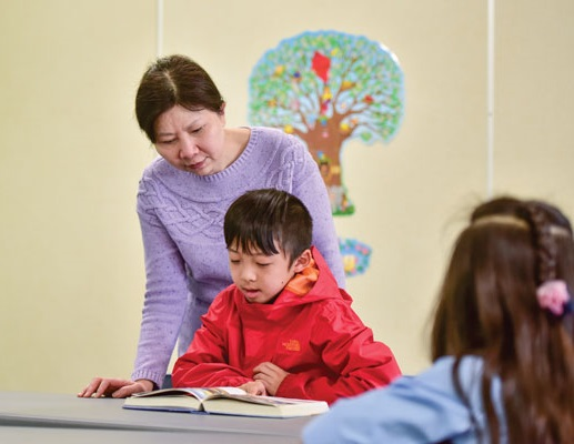 Lillian Lee, Sunday school principal, reads a picture Bible with a young church member.
