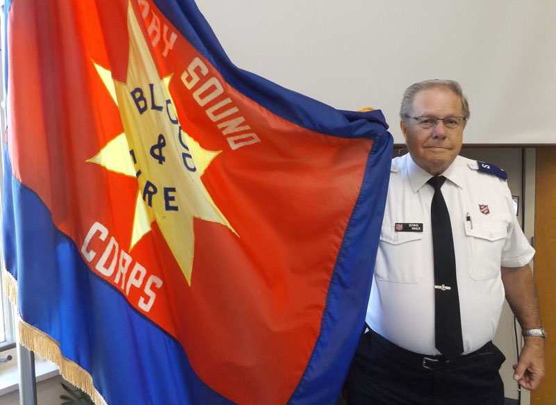 Dennis Miner holds the Army flag as corps sergeant-major at Rainbow Country Church