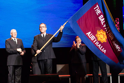 Commissioner Floyd Tidd waves the Army flag at the inauguration of the new Australia Territory as General Brian Peddle looks on