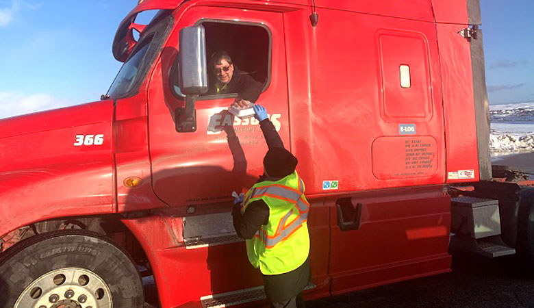 A trucker receiving a hot meal from a Salvation Army personnel in Newfoundland