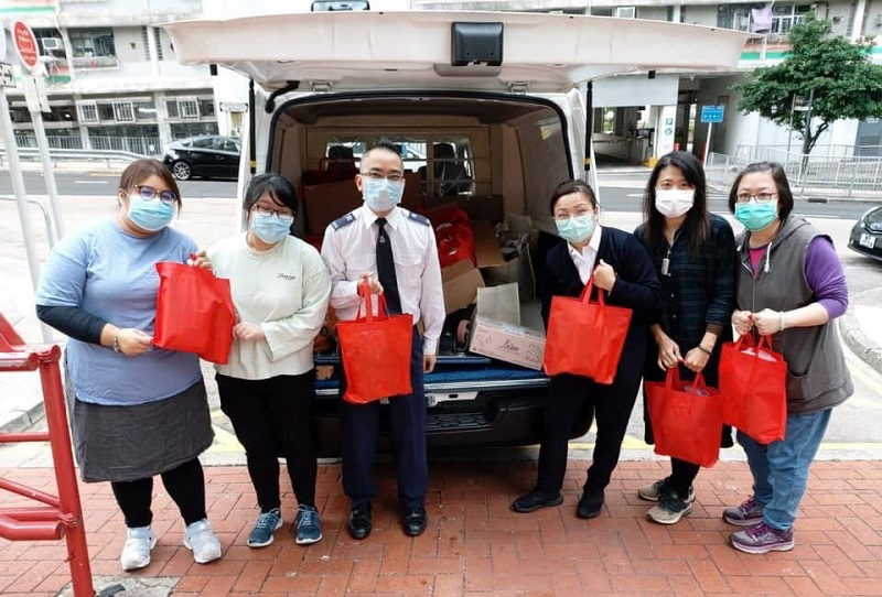 Salvation Army personnel distribute foodstuffs and masks to people in need