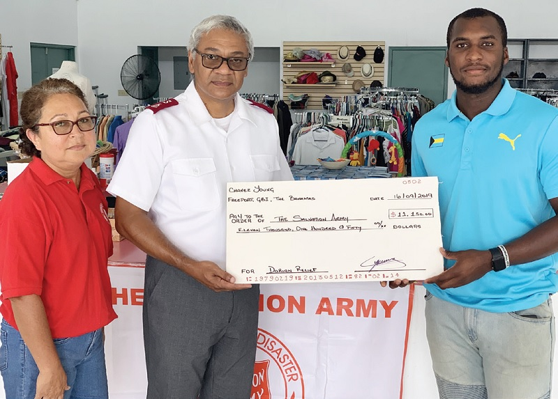 Chavez Young presents a cheque to local Bahamian Salvation Army officers