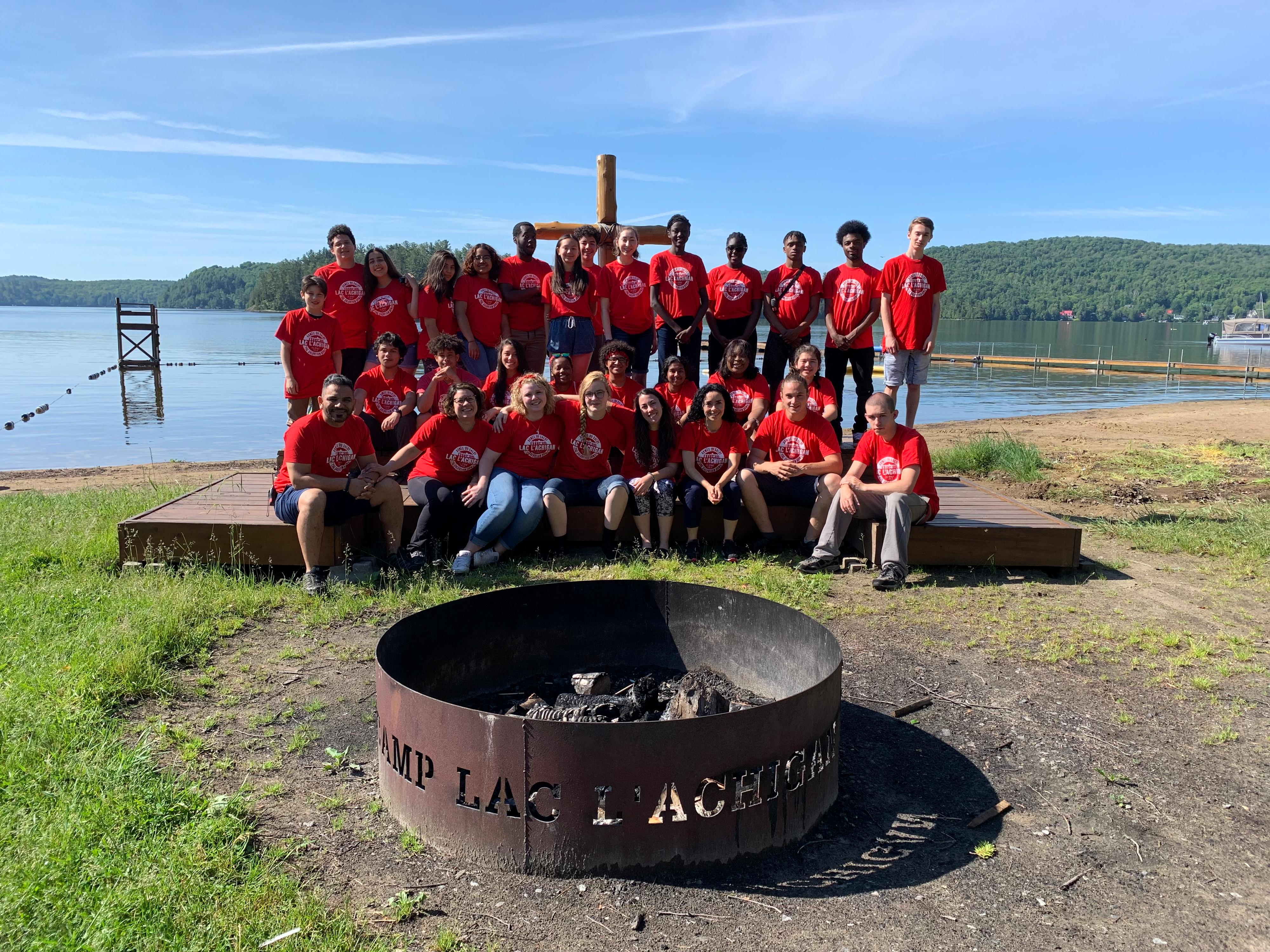 Group photo of staff from Camp Lac L'Achigan in front of a lake with a fire pit in front.