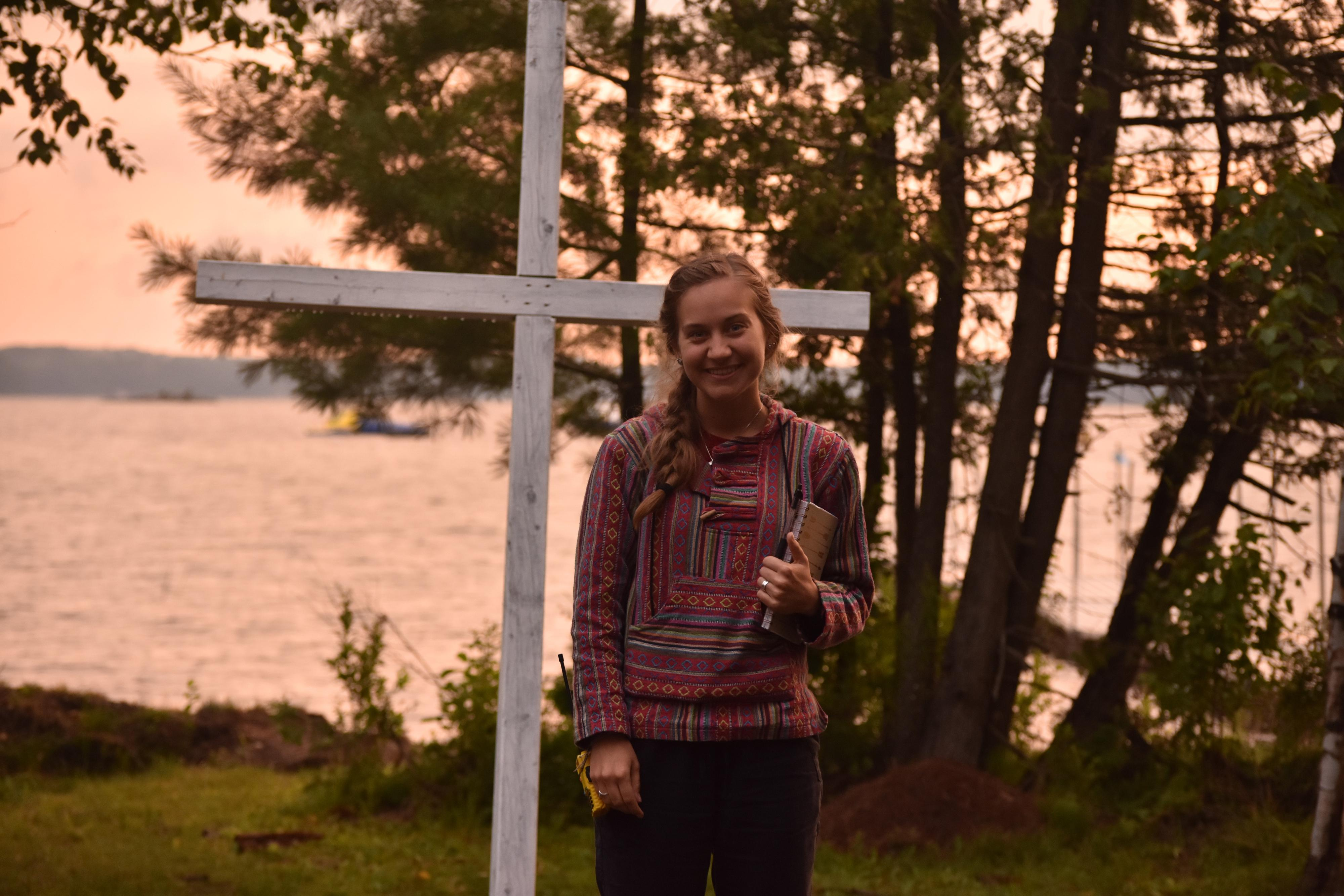 Misha Pavey stands in front of a white cross, holding a notebook, with lake in background