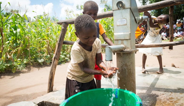A young boy washes his hands at an outdoor water pump