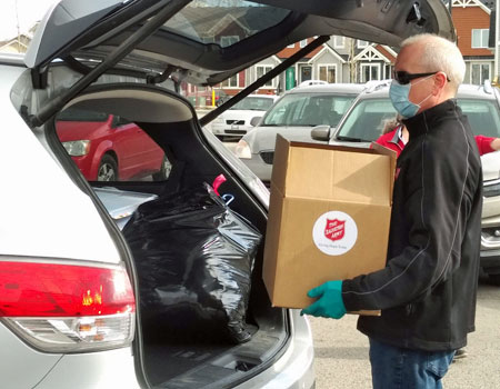 Salvation Army staff wearing a blue mask places a food hamper into the back of a vehicle